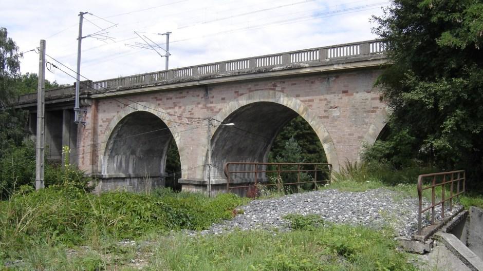 La ligne passait sous le viaduc du Char d'Argent, lequel fût également bombardé en 1944. On aperçoit à gauche une partie du morceau en béton reconstruit du viaduc. Au premier plan, on aperçoit un petit pont. L'ancienne ligne stratégique comportait 5 ouvrages d'art de ce type.